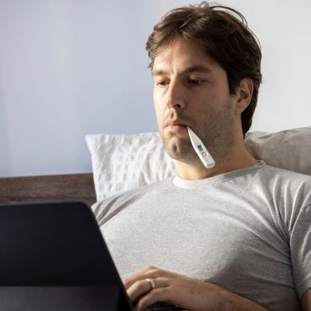 Man ziek bed laptop thermometer