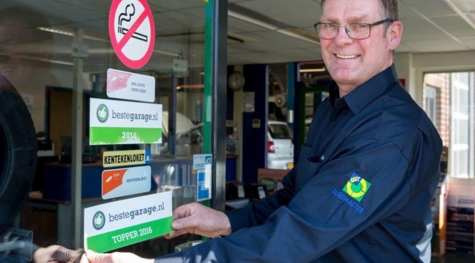 Vestigingsmanager Hans Reimink plakt het predikaat op de deur foto Beste Garagenl 1